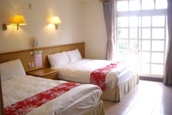 Yilan - Toucheng Farm International YH : Yilan - Toucheng Farm International YH hostel interior twin room, well-lit, with patio doors, pretty white and red floral bedspreads