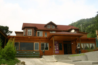 New Life Spring Resort - Hualien : New Life Spring Resort - Hualien, hostel exterior, wooden cabin style building surrounded by trees