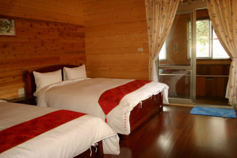 New Life Spring Resort - Hualien : New Life Spring Resort - Hualien, hostel interior, twin room, warm and cosy feel, with wooden panelling, 2 double beds with red and white bedsheets