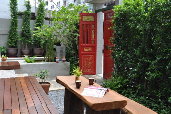 HI Udee Bangkok : HI Udee Bangkok hostel garden with wooden benches and tables, plants and traditional red Thai gates