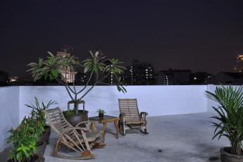 HI Udee Bangkok : HI Udee Bangkok hostel rooftop terrace at night with recliners, overlooking the city