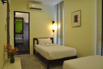 HI Udee Bangkok : HI Udee Bangkok, twin room with green and white decor, minimal design, 2 single beds and a door open hat shows the bathroom