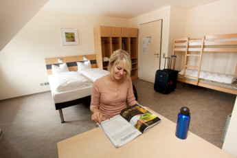 Petershagen : Petershagen Hostel guest reading in a dorm room with a double bed and bunk beds