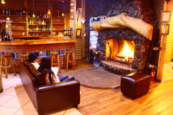 Chillán - Chil In : People Relaxing by the Fireplace in the Bar and Lounge Area in Chillan - Chil In Hostel, Chile During the Snow