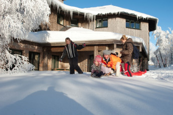 Torfhaus : guests playing in the snow outside peat bog house Hostel, Germany