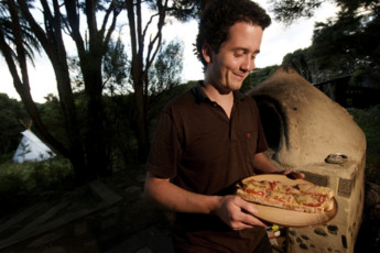YHA Raglan : Guest Making Pizza on the Barbecue at Raglan YHA - Solscape Eco Retreat Hostel, New Zealand