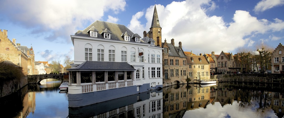 Scenic waterways thread through cobbled streets lined with medieval architecture and dotted with picturesque squares in charming Bruges.