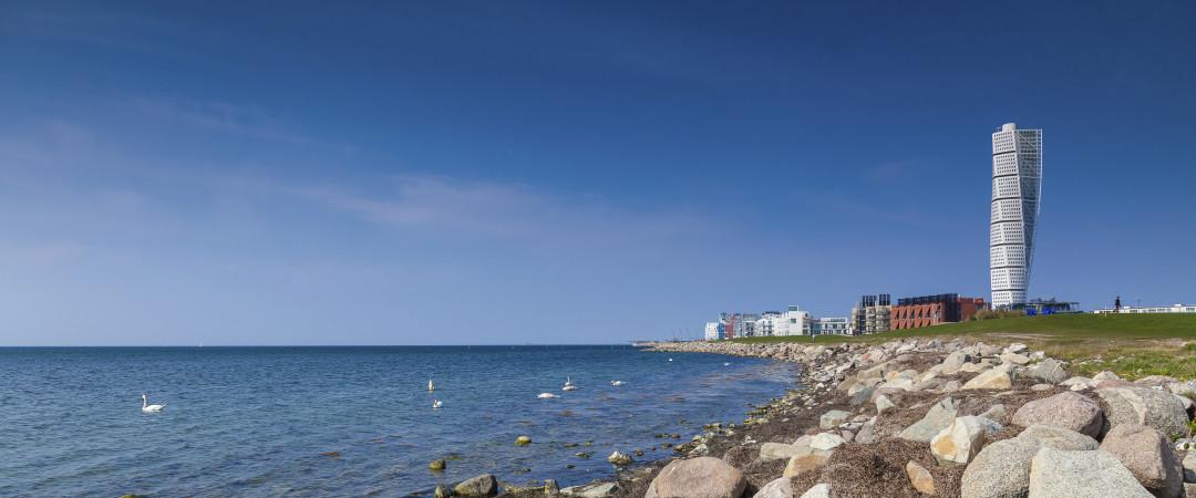 Tomar una toalla y descansar en la playa de Malmö mientras disfruta de la vista de un magnífico el rascacielos Turning torso cubierto, una de las maravillas de Suecia.
