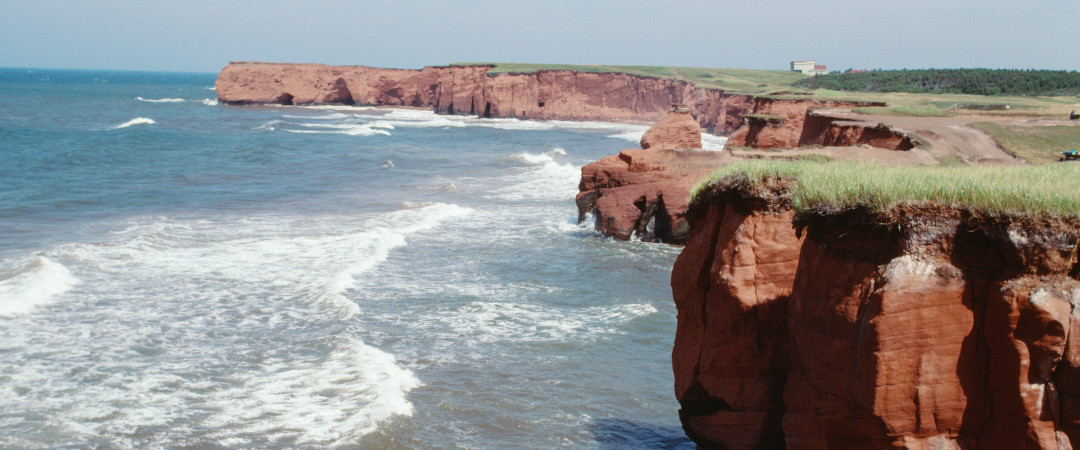 The famous red cliffs of Îles de la Madeleine look especially stunning with the waves of the Gulf of Saint Lawrence crashing against them.