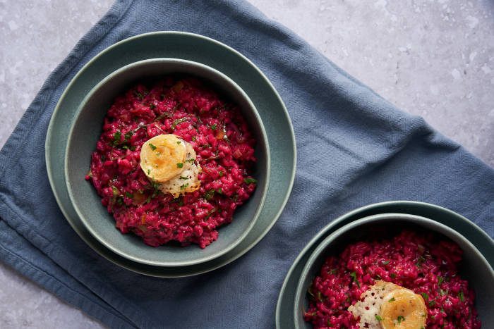 Two bowls of beetroot risotto with goats' cheese garnish