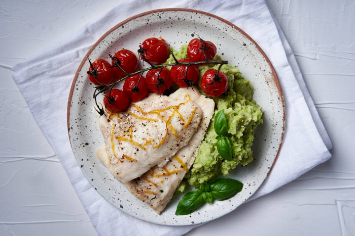 A plate of cod, basil bean mash and tomatoes