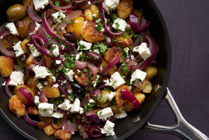 Potatoes, onion, feta and olives in frying pan