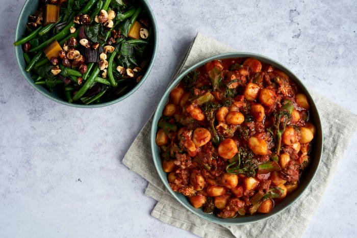 Sausage gnocchi with hazelnut and bacon topped greens