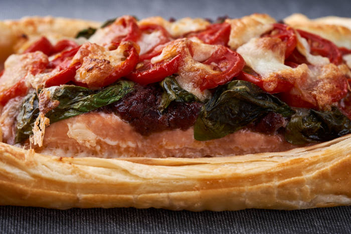 Side view of pastry, salmon, tapenade, basil, tomatoes and mozzarella
