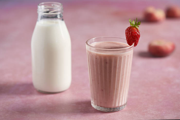 A glass of strawberry and peach kefir smoothie