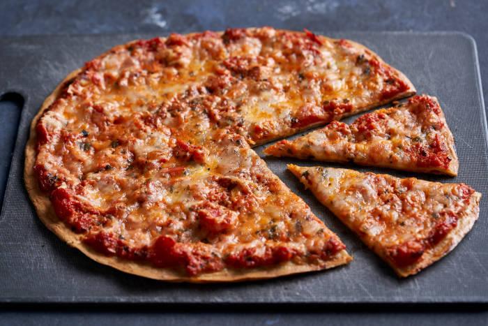 Quinoa pizza crust topped with tomato sauce and mozzarella