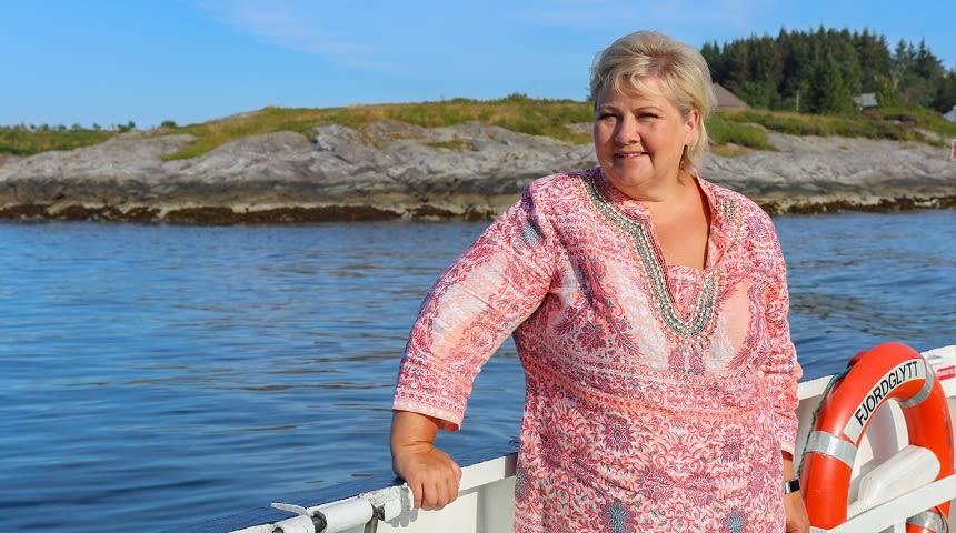 Erna Solberg ombord i båt, kystlandskap i bakgrunnen.