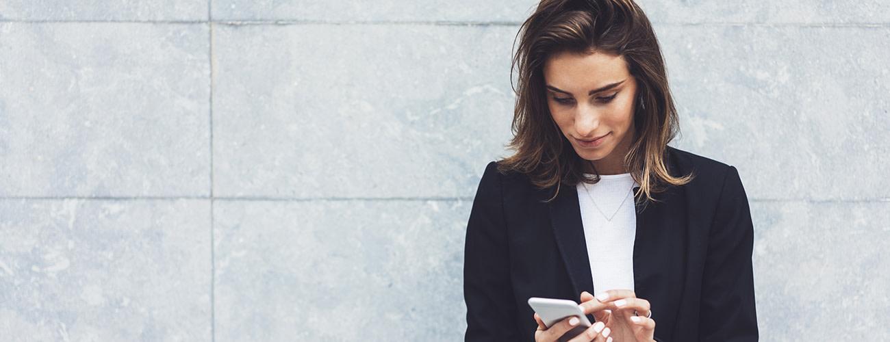 Woman using smartphone against grey brackground