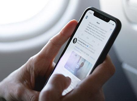 Persoon bekijkt Twitter op een iPhone in het vliegtuig