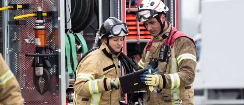 Two firefighters holding a tablet