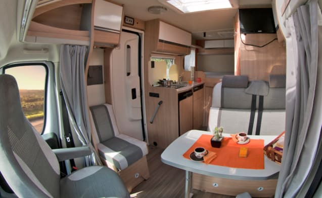 Compact luxury motorhome with fixed double bed.