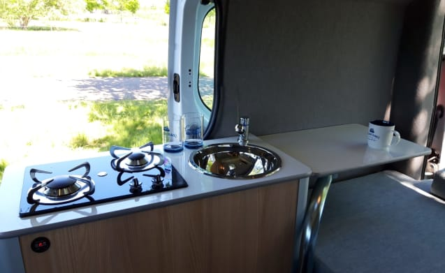 Luxury compact motorhome with indoor / outdoor cooking and light and spacious interior.