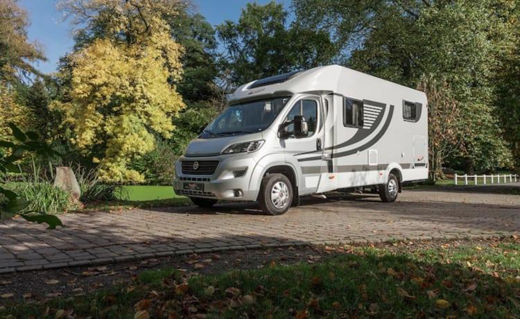 Compacte luxe camper met vast 2-persoonsbed.