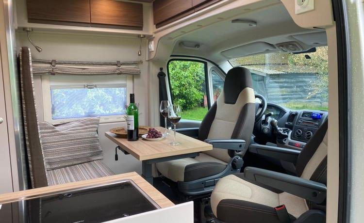 Autobus camper Fiat Ducato con sedili di lusso e un grande letto matrimoniale.