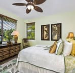 Main floor bedroom with queen bed decorated in a serene coconut palm motif.