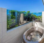 West master bathroom outdoor area with natural stone Balinese soaker tub