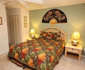 Master bed with island theme, coral end tables, remote control air, phone, clock