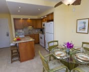 Showing the kitchen, island, and dining table, along with dining area and fan
