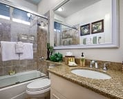 Main floor bath with vanity, granite counter and full tub and shower.