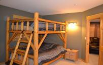 One of two queen bunk beds in basement.