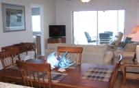 View from kitchen through dining room.  Large flat-screen TV, DVD and stereo in living room
