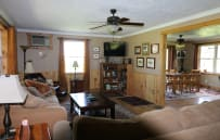 Family Room view from front door entry.  Two sofas, a chair with ottoman for relaxing and a  flat screen TV with cable