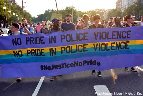 People holding a banner that says No Pride In Police Violence (twice) then #NoJusticeNoPride