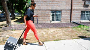 A female CU researcher walks along a sidewalk pulling a rolling bag of equipment behind her in front of a brick apartment building in Aurora, Colorado.