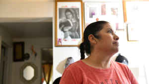 A mother listens in her living room to CU students and researchers as they explain the research project. A picture of the Virgin Mary hangs behind her on the wall.