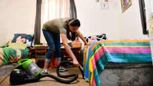 A teenage girl bends over to vacuum the carpet in her bedroom that she shares with her sister