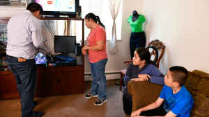 A CU student unwraps two air sensors to place them in the living room of a family; the mother stands by and a two children, a middle school age girl and elementary school age boy, by the couch look on.