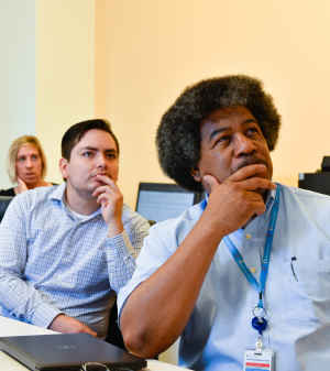 Two men, a student and a community health expert, listen with their hands to their mouths during a meeting about the research project.