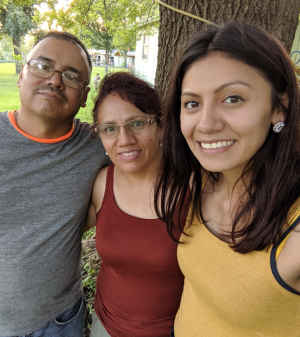 A female CU student stands side by side with her father and mother during a backyard barbecue.