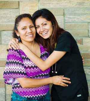 A CU medical student in her scrubs and with a stethoscope smiles and embraces her mother