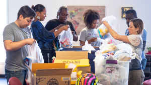 A group of CU students and researchers stand at a table filled with boxes and help community organizers put chips, granola bars and toothbruches into plastic bags to deliver to the neighborhood residents.