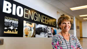 """A female faculty member stands in front of a """"Bioengineering"""" sign in a hallway on the CU Denver campus."""