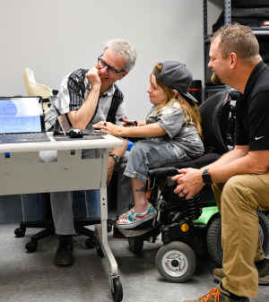 A young woman sits in her motorized wheelchair and works on a laptop as two CU staff members look on and smile. They discuss how to improve her wheelchair.
