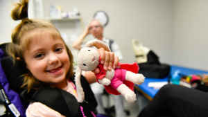 A young girl holds up to show off her beloved stuffed toy, a faded pink bunny, and smiles.