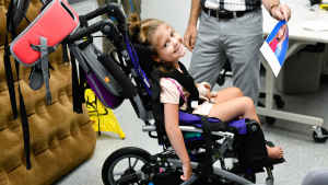 """A young girl sits in an oversized stroller and smiles over her shoulder. The occupational therapist shows her a paper printout of the two princesses from the movie """"Frozen."""""""