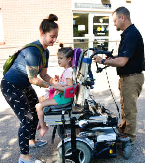 Outside in a parking lot, a mother straps her young daughter into a motorized wheelchair as a clinic staff member makes adjustments.